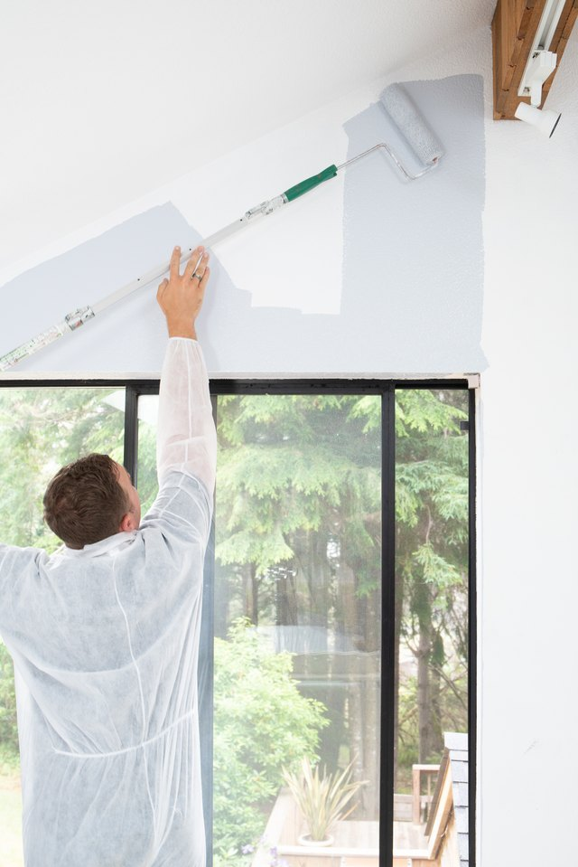 Man painting interior of home with roller