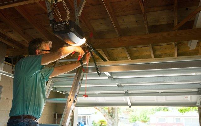 Professional automatic garage door opener repair service technician man working
