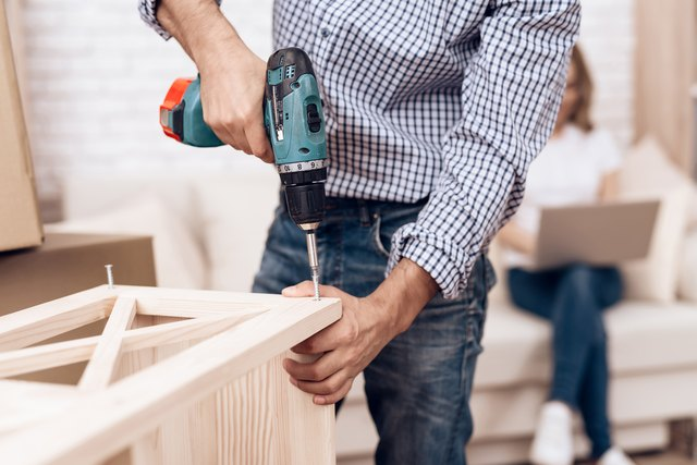 Man handyman is engaged in assembly of furniture. Repairman is engaged in repairing furniture.