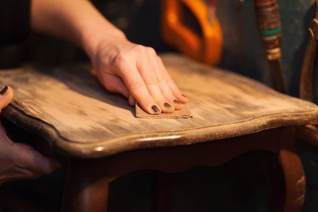 Close-up of woman sanding table top.