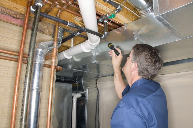 Home inspector inspecting pipes