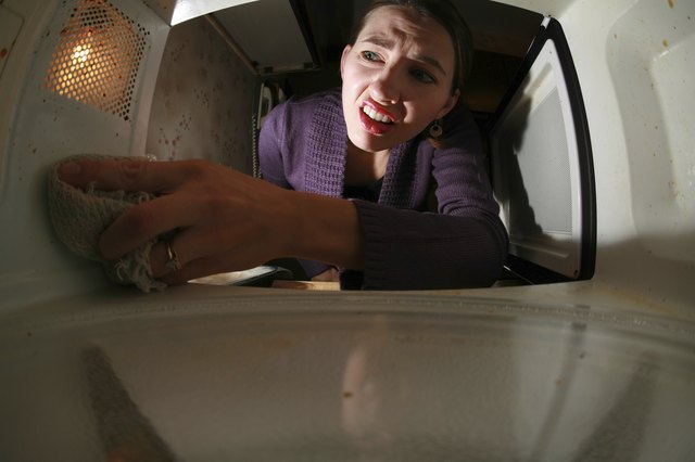 A disgusted woman cleaning the inside of a dirty microwave oven.