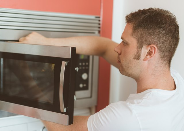 Male technician repairing microwave oven.