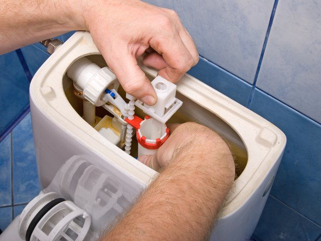 Plumber repairing the mechanism of a toilet