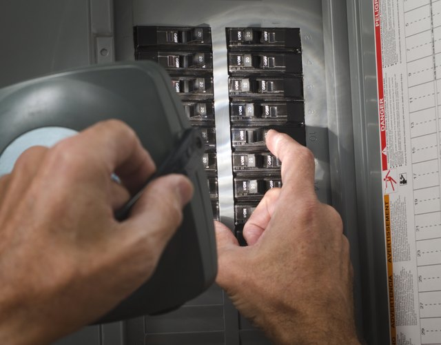 Man with flashlight at residential circuit breaker panel.