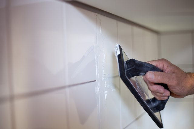 A Kitchen Fitter, tiling the walls