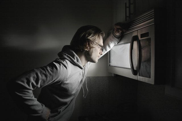 Young man looking in microwave window, side view