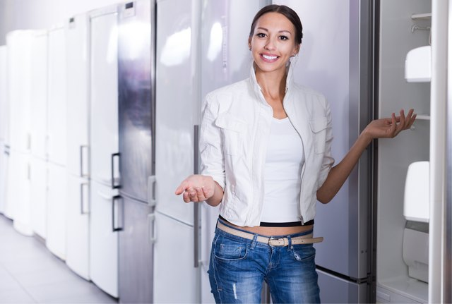 Woman choosing new refrigerator in shop
