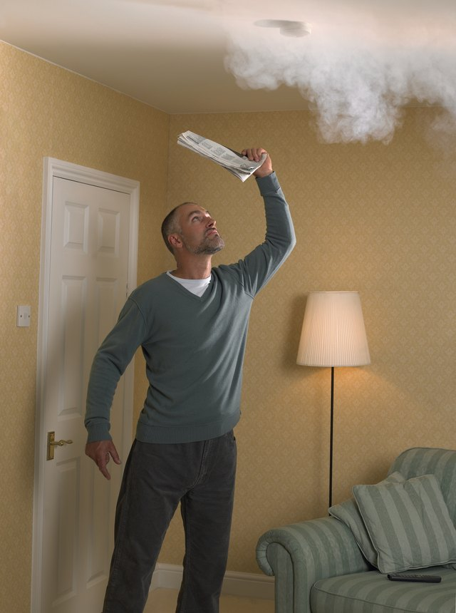 Man fanning smoke detector with newspaper