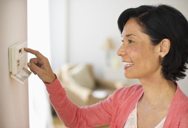 USA, New Jersey, Jersey City, Mature woman adjusting room temperature