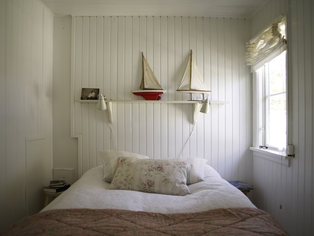 Bedroom with white wood panelling and bed