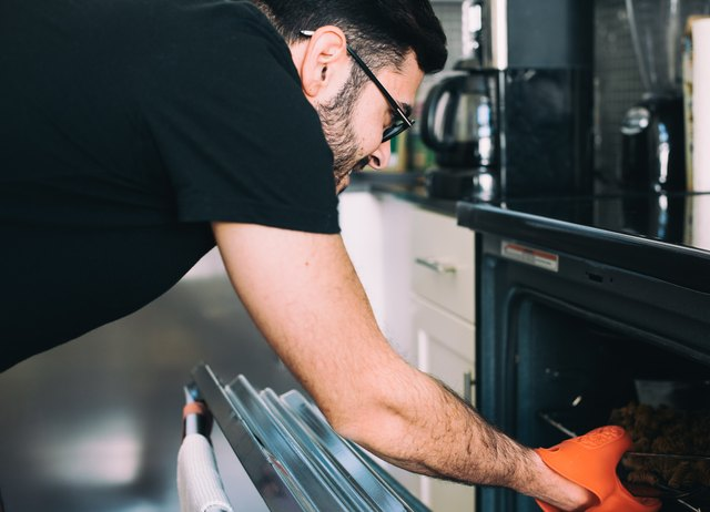 Man removing food from oven
