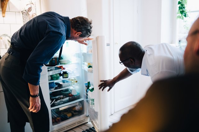 Mature male friends looking into refrigerator at kitchen