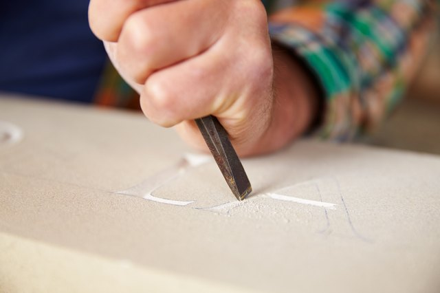 Close Up Of Stone Mason Working On Carving In Studio