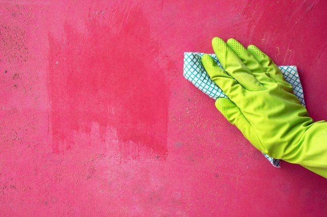 Close up of person hand cleaning mold fungus from wall using rag