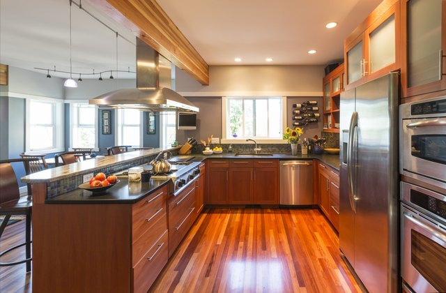 Contemporary upscale home kitchen interior with wood cabinets and floors