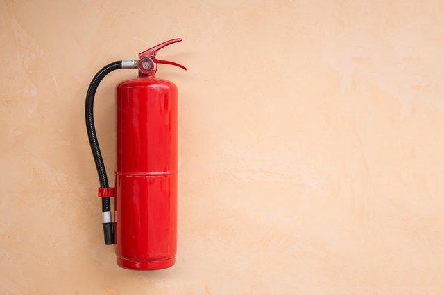 Red fire extinguisher tank on orange wall