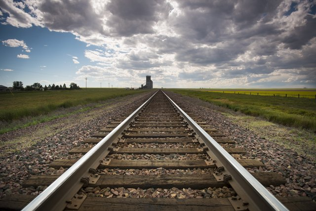 railroad tracks recede to the horizon, dark summer sky approaching