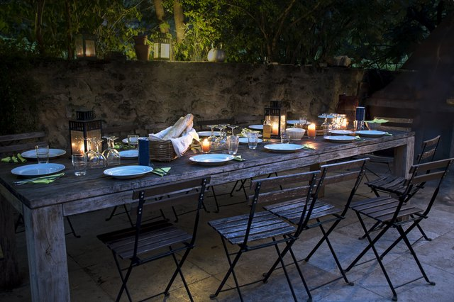 large rustic table prepared for a outside dinner at night