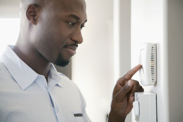 Man adjusting thermostat