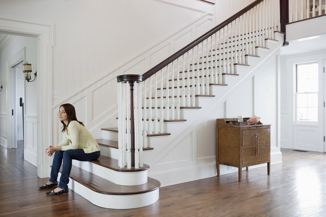 Mid adult woman sitting on stairs in entrance hall