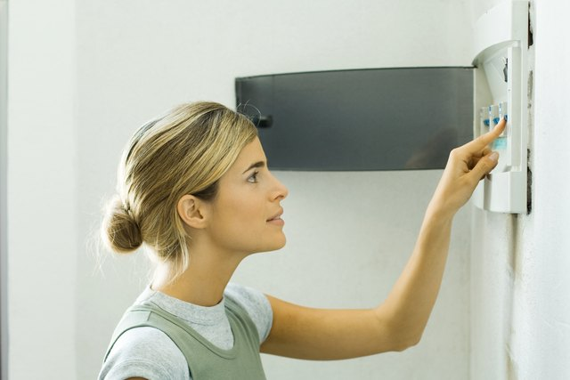 Woman pushing lever in fuse box