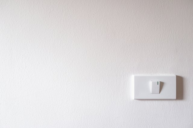 light switch on white concrete wall