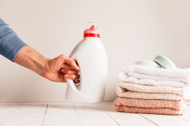 Man's hand putting on the table a jar of gel for washing clothes. Against the background of a pile of towels and soap