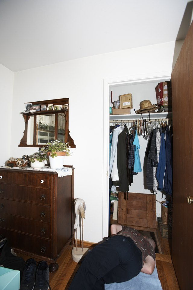 Young man lying on floor, looking down into crawl space in closet