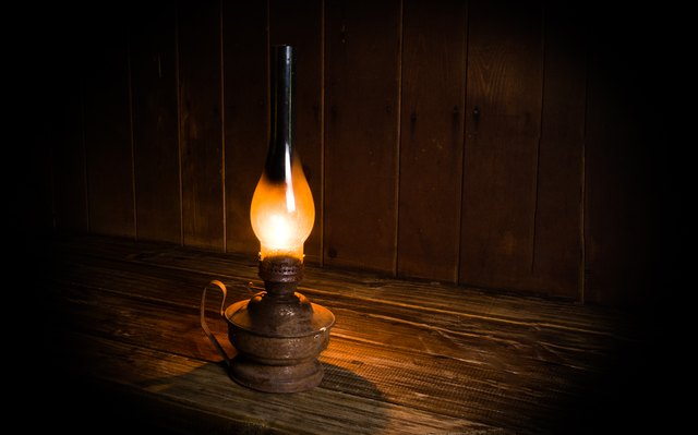 Antique burning paraffin lamp near on the wooden table.