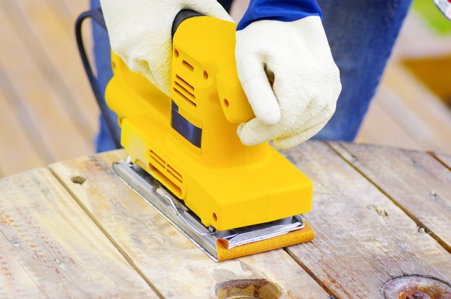 eyellow electric sander over a wood table