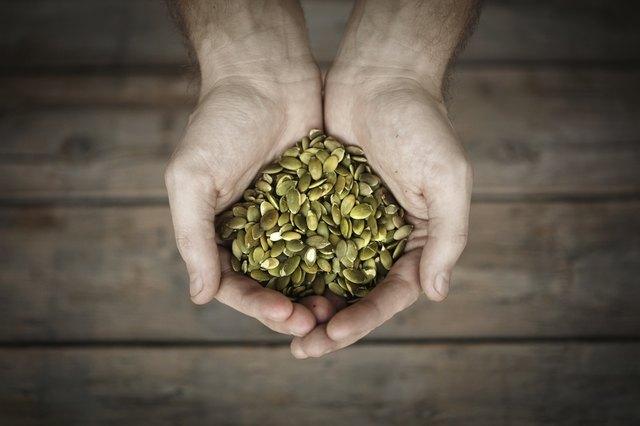Pumpkin seeds in mans hands, close-up