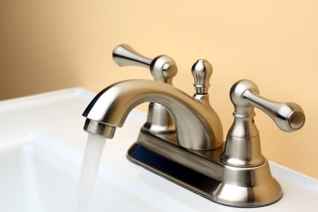 Water flowing from Brushed Nickel Faucet on Porcelain Bathroom Sink
