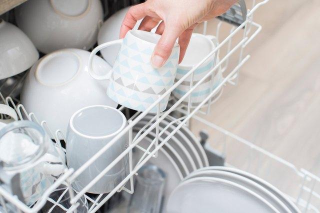 Close Up Of Woman Loading Crockery Into Dishwasher