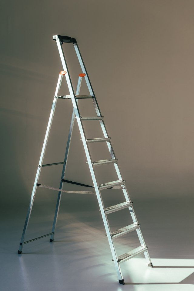 open metallic stepladder in studio on grey