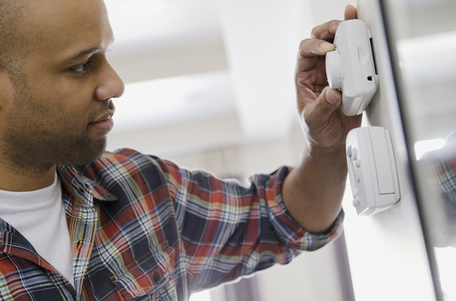 homeowner adjusting new thermostat