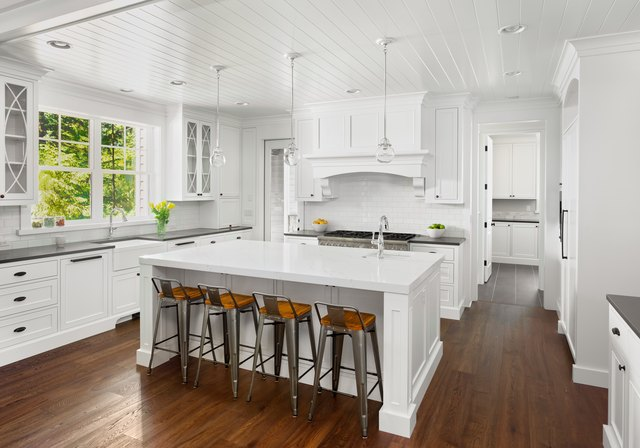 beautiful white kitchen in new luxury home with island, pendant lights, and hardwood floors