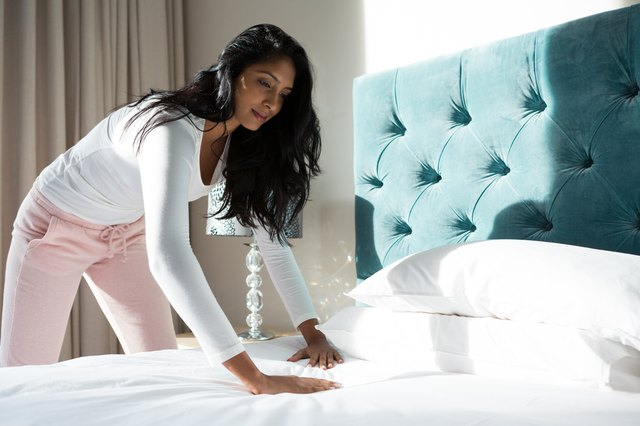Young woman making bed