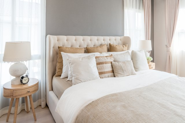 Bedroom in soft light colors. big comfortable double bed in elegant classic bedroom at home.