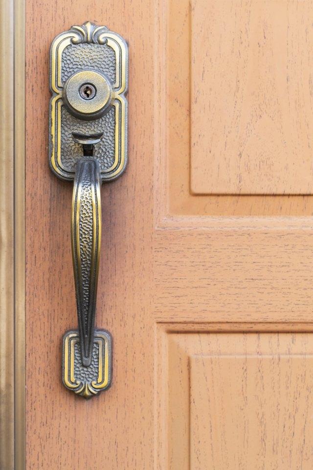 Antique metal door handle and brown wood door.