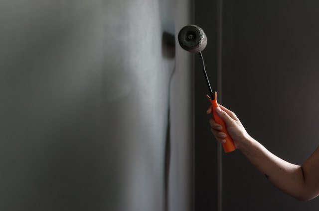 Hand holding paint roller applying grey paint on wall.