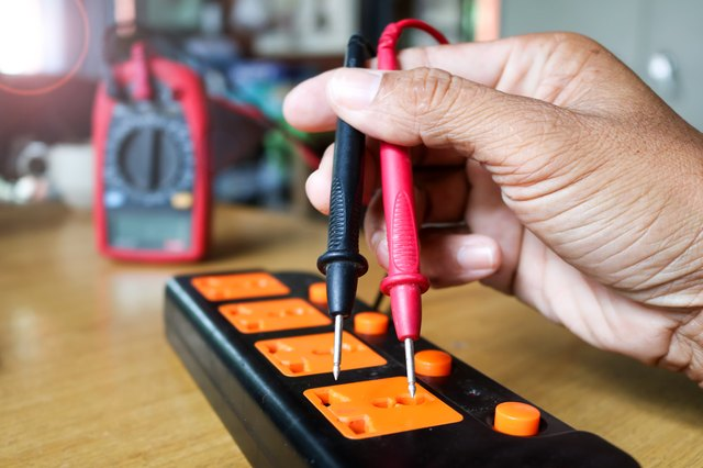 Worker use voltmeter measure the current from extension plug