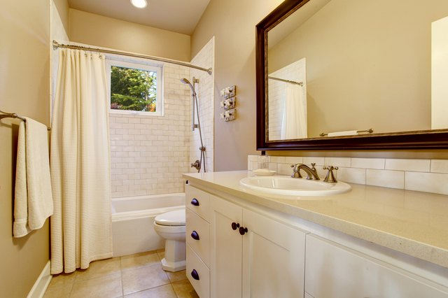 Light bathroom interior with white cabinet and shower