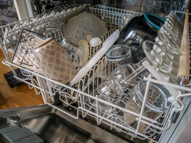 Open dish washer is done. Clean glasses and kitchen ware. Modern style.