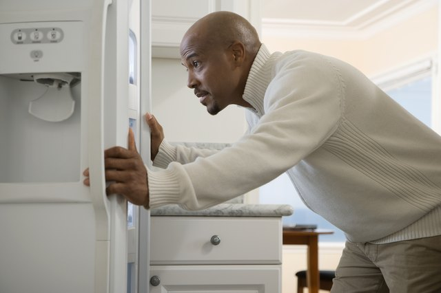 African man looking in refrigerator