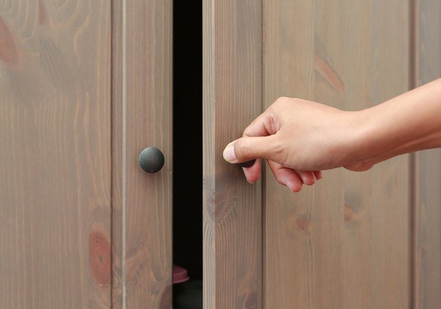 Woman Hand Opening Cabinet Doors.