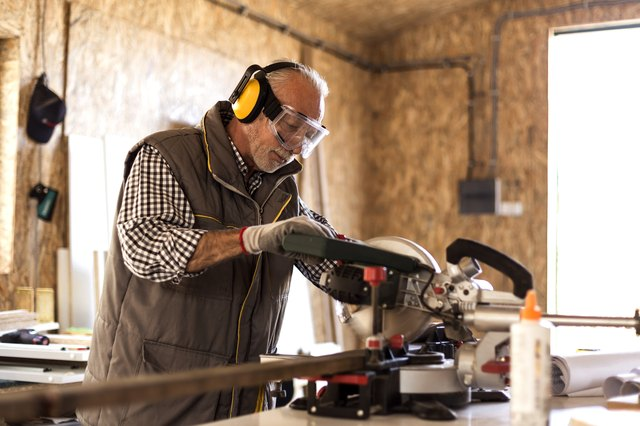 Mature carpenter using circular saw in his workshop