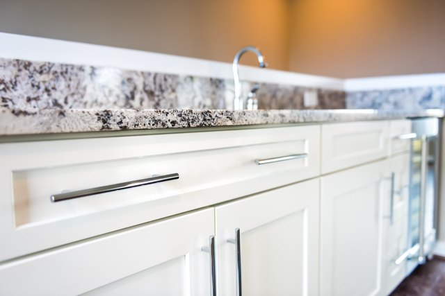 Modern clean wet bar with granite countertop cabinets, faucet in model house, home or apartment, mini fridge