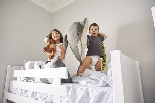 Portrait Of Children Playing With Toys In Bunk Bed