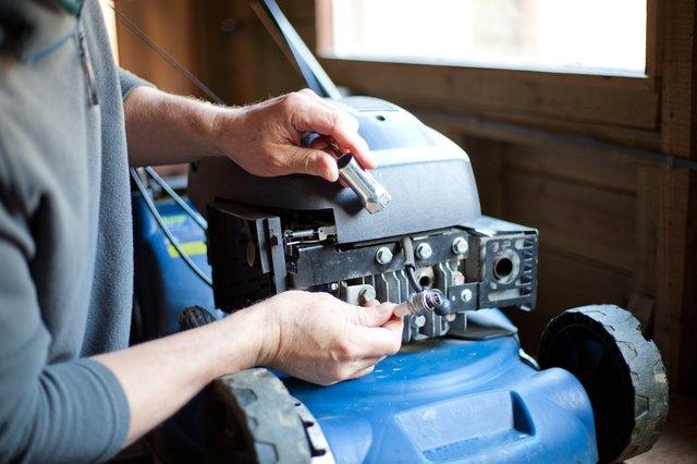 A man repairing a petrol lawn mower